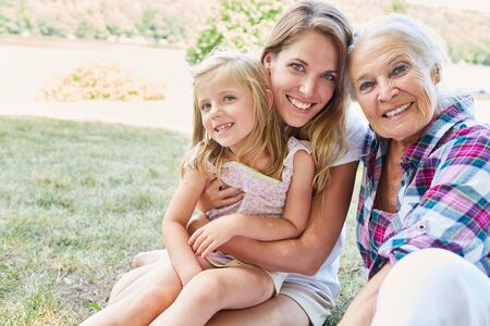 Women of a family in three generations with mother between grandmother and granddaughter
