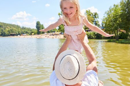 Father lifts daughter up on a boat trip on the lake in the summer in amusement park