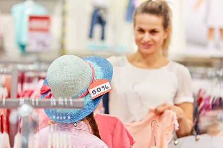 Woman and child in hat. Shopping during a sale action