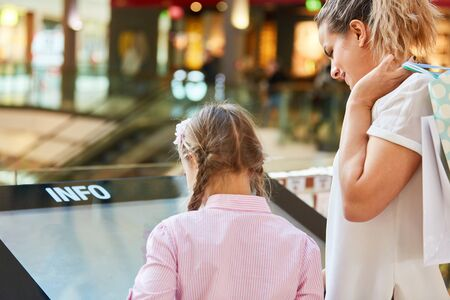 Family is looking for shops on the touch screen Information kiosk in the shopping center