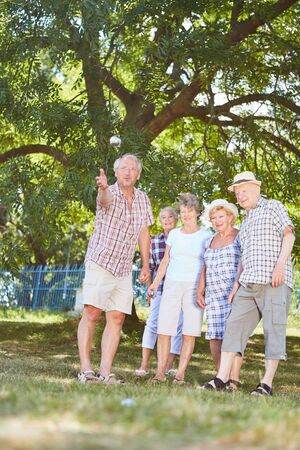 Seniors play boule or bocce together in the garden of the retirement home in the summer