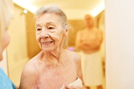 Old woman in the wellness department of the senior residence is looking forward to the sauna Stockfoto
