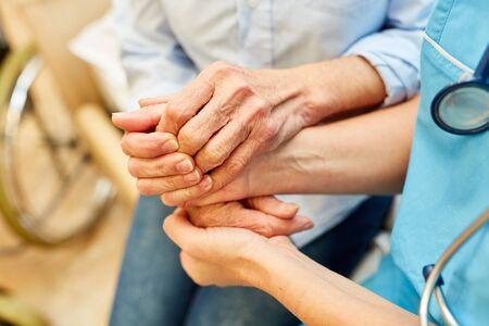 Nursing help keeps the hands of a senior citizen in a nursing home or nursing