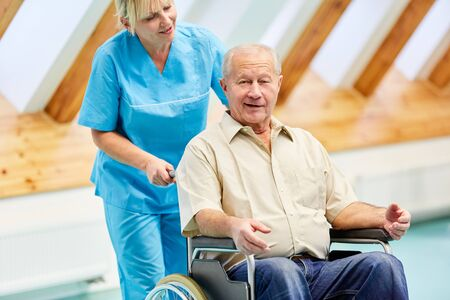 Senior man after stroke in wheelchair is cared for by nursing assistant caring