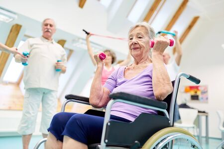 Senior woman in wheelchair exercises fitness with dumbbells in a rehabilitation group Foto de archivo - 133052100