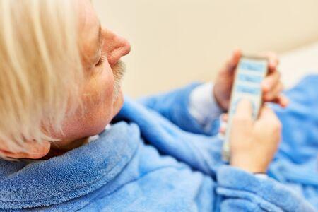 Sick senior in nursing bed with remote control in nursing home or nursing home