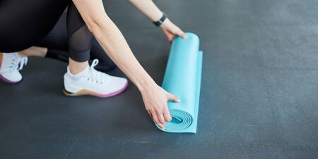 Young woman rolls up a yoga mat after fitness workout