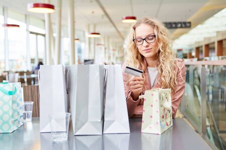 Young woman as a customer while shopping with credit card or customer card
