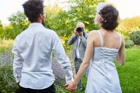 Wedding photographer takes pictures of newlyweds in nature on wedding day