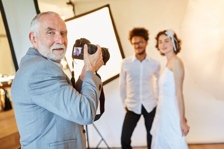 Experienced wedding photographer takes pictures of the newlyweds on the wedding day Foto de archivo