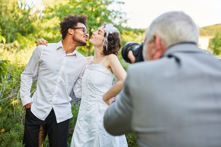 Wedding photographer photographs newlyweds kissing on the wedding day