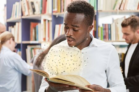 African man looks in wonder at a glowing book with flying letters 版權商用圖片