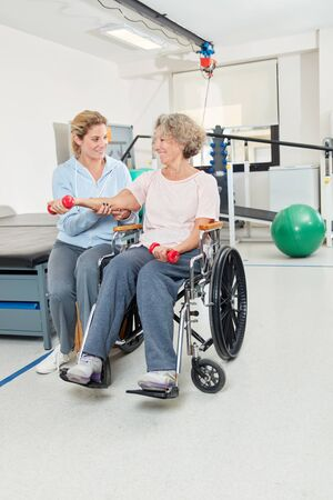 Woman in a wheelchair doing dumbbell training and being looked after by an occupational therapist