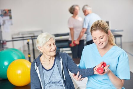 Caring physiotherapist helps a senior dumbbell in rehabilitation Reklamní fotografie