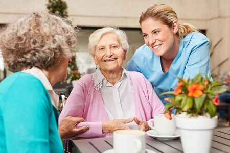 Senior women in retirement home in conversation with a nurse at the coffee table Reklamní fotografie - 133704404