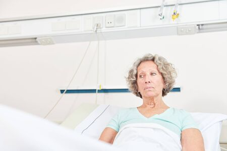 Woman as an unhappy patient lies in the hospital bed and looks worried Reklamní fotografie - 133704521