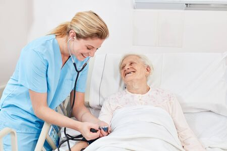 Nurse or nurse checks the blood pressure of a senior citizen
