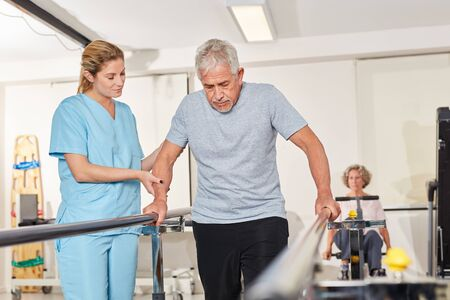 Physiotherapist helps senior man with rehab on the treadmill Reklamní fotografie