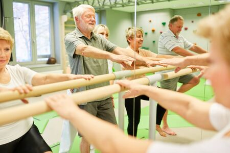 Group of seniors at rehabilitation physiotherapy on a ballet bar in front of the mirror Foto de archivo