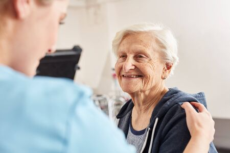 Therapist motivates sick elderly woman as rehab patient in physiotherapy Reklamní fotografie - 133704694