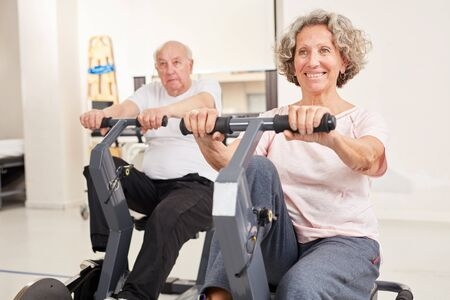Senior couple doing endurance training while rehabilitation sport on the ergometer