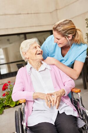 Happy senior woman in wheelchair with caregiver in rehab or nursing home Reklamní fotografie