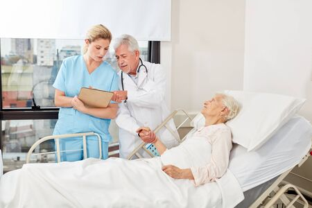 Doctor and nurse discuss therapy at the bedside of a senior citizen
