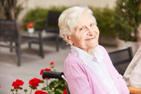 Happy senior retired woman in retirement home or nursing home