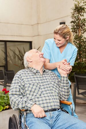 Nurse caregiver cares for senior man in wheelchair at rehab clinic