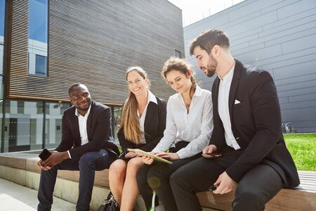 Group of business people as a team with a tablet computer in front of the corporation