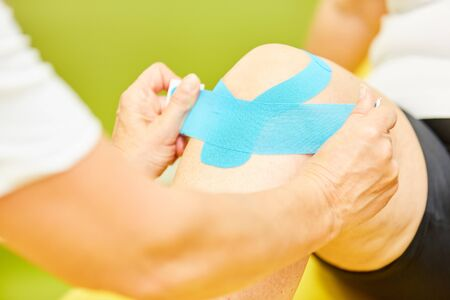 In Physiotherapy, a man gets a kinesio tape on his knee joint for knee pain