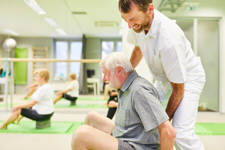 Physiotherapist gives senior assistance with an exercise in the back school in Reha course Standard-Bild
