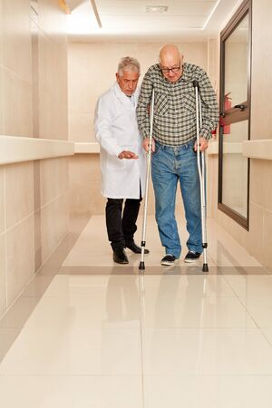 Doctor accompanies senior man on crutches in rehab clinic while learning to walk