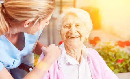 Laughing elderly woman with a caring nurse in a retirement home