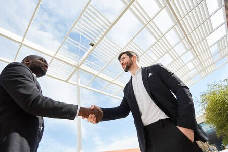 Two business men shake hands and form a partnership