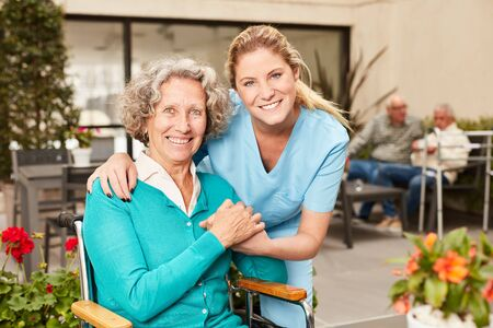 Happy senior woman and nursing assistant or geriatric nurse in retirement home