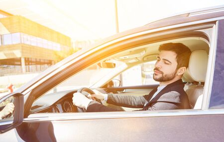 Businessman driving in the car with his hands on the steering wheel Banco de Imagens