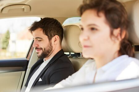 Young couple in the car on the road on business trip or drive to the office