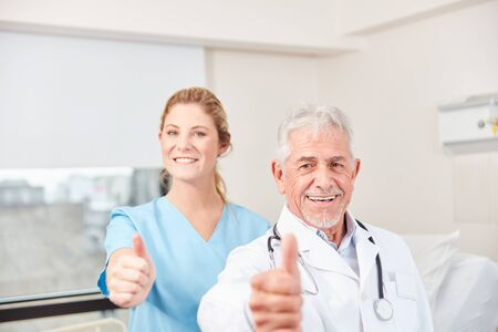 Doctor and nurse as successful clinic team with thumbs up