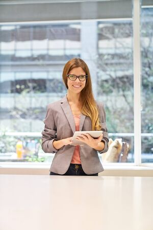 Young business woman or trainee with tablet computer in the office