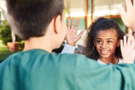 Happy girl gives her friend a high five for friendship
