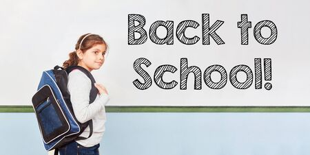 Back to school with girls and satchels in front of a whiteboard in a primary school Stockfoto