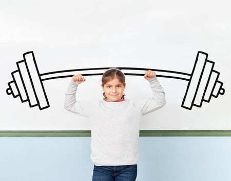Girl at school balles fists in front of a barbell on the whiteboard Stock Photo