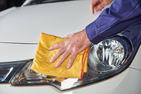 Mechanic hand with cloth while brushing and polishing to paint care of car