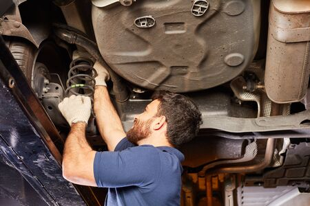Mechatronics inspects or repairs car shock absorbers during an inspection