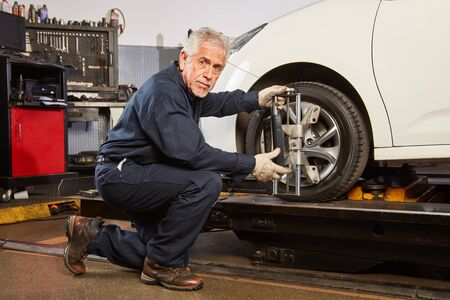 Experienced mechanic makes a wheel alignment in the auto repair shop
