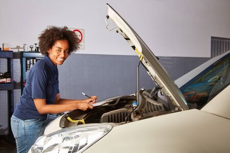 Smiling African woman as a mechatronics apprentice with checklist for the inspection Reklamní fotografie