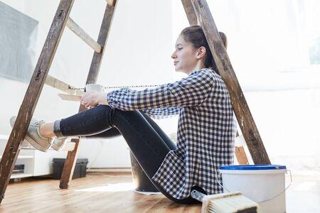 Eine junge Frau als Heimwerker macht eine Pause beim Renovieren ihres neuen Zuhauses Standard-Bild