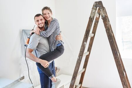 Amorous young couple with drill and ladder while renovating in new house