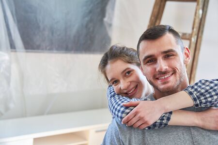 Happy young couple is happy about moving to new home or new apartment